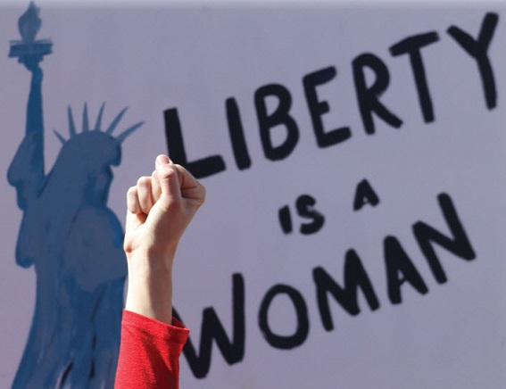 Woman's fist raised before a sign reading 'Liberty is A Woman'