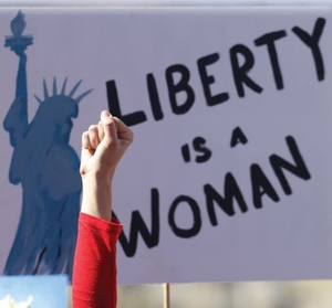 Image of a raised fist with a sign behind it that states Liberty is a woman