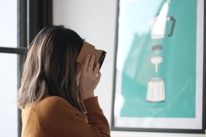 Person with long hair looking at a 360 video through a Google Cardboard