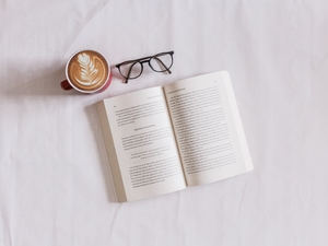 Open book, latte, glasses on white background